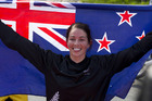 Sarah Walker holds the New Zealand flag after winning silver in the women's BMX race. Photo / Brett Phibbs