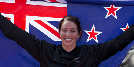 Sarah Walker holds the New Zealand flag after winning silver in the women's BMX race. Photo / Brett Phibbs