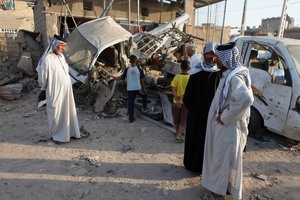Iraqis inspect the aftermath of a car bomb that exploded near the town of Suwayrah. Photo / AP