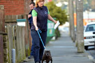 Animal control officer Roz McDonald removes a dog which bit a 1-year-old girl at the family's Oxford St, South Dunedin, home yesterday. Photo / Peter McIntosh