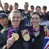 New Zealand's Jo Aleh, left, and Olivia Powrie jubilant with team mates after receiving the gold medal for the Olympic women's 470 dinghy sailing. Photo / Mark Mitchell NZ Herald