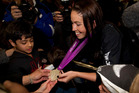 Sarah Walker shows her Olympic medal to fans at Auckland International Airport. Photo / Steven McNicholl