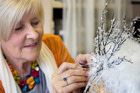 Master milliner Carolyn Gibson adds some finishing touches to one of her creations. Photo / Natalie Slade
