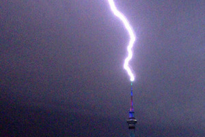 Lightning hits the Sky Tower around 00:45am today, as seen from Freemans Bay. Photo / David Li