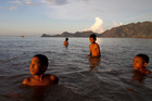 Timorese boys swim in the ocean by a city beach in Dili, Timor-Leste. Photo / Getty Images