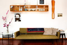 Heath Lowe's European green sofa bed with wall unit in the living room of his Birkenhead home. Photo / Babiche Martens