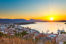 Watching the sun set while sipping beer in Poros, Greece, ranks as one of travel's great pleasures. Photo / Getty Images