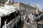 Men collect parts of a damaged bus which was hit by a remote control bomb. Photo / AP