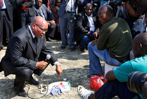 South Africa's President Jacob Zuma, left, interacts with striking mine workers at the Lonmin mine near Rustenburg. Photo / AP