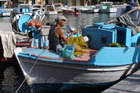 Fisherman mend nets from their blue and white wooden caiques in Symi's harbour. Photo / Lois Green