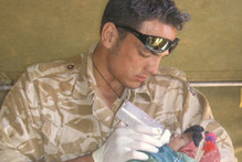 Lance Corporal Luke Tamatea feeding a baby nutrient formula. Photo / Supplied