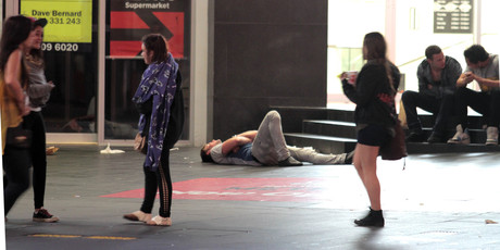 A youth collapses on Queen St in the early hours of the morning. Photo /  Geoff Dale