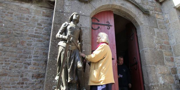 A woman addresses the statue of Joan of Arc outside the parish church on Mont St Michel.  Photo / Jim Eagles