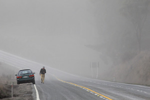 A motorist is surrounded by a cloud of ash on state highway one after Mt Tongariro erupted earlier this month. Photo / Hagen Hopkins