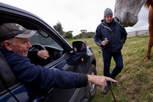 Jamie Lockett (standing) talks to farmer David Steele on the newly purchased Waimauku block yesterday before telling him to leave. Photo / APN