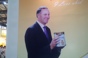 John Key unwittingly endorsing a milk powder formula made by Chinese company abid. Photo / Supplied