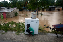 A boy tries to take cover from the cold behind an appliance sitting higher than the floodwaters triggered by Tropical Storm Isaac in Port-au-Prince, Haiti. Photo / AP