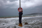 A man stands on a post with a stop sign as waves pass the seawall during the passage of Tropical Storm Isaac in Baracoa, Cuba, Saturday, Aug. 25, 2012. Tropical Storm Isaac pushed into Cuba on Saturda