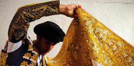 A Spanish bullfighter adjusts his 'capote' as he prepares for action. Photo / AP