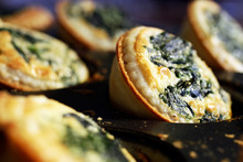Spinach and parmesan quiches are the perfect bite-sized treat. Photo / Michael Craig
