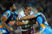 Manly's Steve Matai is wrapped by the Titans defence last night. Photo / Getty Images