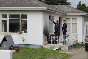 Police forensically examine the property on Amyes Road which was attacked by a molotov cocktail. Photo / The Star