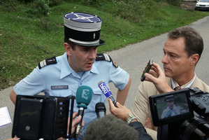 Eric Maillaud (right) and a police colonel answer questions near the murder scene yesterday. Photo / Alexis Moro