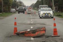 Cars drive around manhole covers in Brooklands moved by the earthquake in September 2010. Photo / Alan Gibson