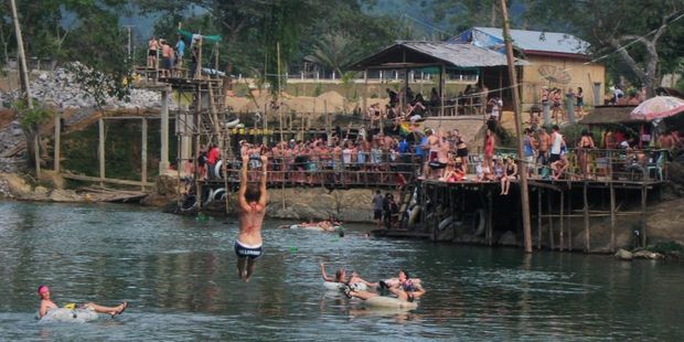 Travellers stop at bars to knock back free shots of potent Lao whisky while tubing down the Nam Song River in Vang Vieng. Photo / Thomas Bishop