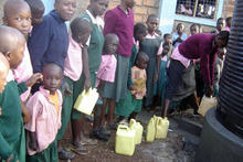 Students at Ikoba Primary School in Kenya line up at a water tank donated directly to them by School Aid. Photo / Supplied
