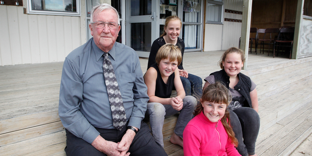Murray Thompson, 79, with Pukeatua School pupils (from left) Mika Harris, Nikita Beck, Emma Anderson and Julia Mickell on the steps of the Matapihi Education Centre where he's a volunteer. Photo / Christine Cornege
