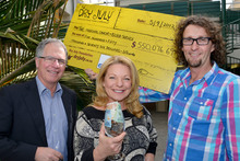 Kerre Woodham hands over more than $550,000 to Dr Richard Frith, left, and Dr Richard Sullivan. 