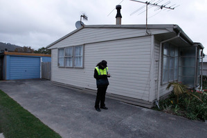 A security guard on duty in the back yard of a house where the body of a newly born baby was discovered in Taita Drive, Lower Hutt. Photo / Mark Mitchell