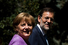Spain's Prime Minister Mariano Rajoy walks with German Chancellor Angela Merkel in Madrid. Photo / AP