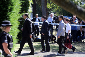 The media watch as British and French police officers arrive at the home of Saad al-Hilli, in Claygate, England. Photo / AP