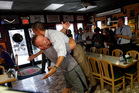 President Barack Obama, right, is picked-up and lifted off the ground by Scott Van Duzer, left, owner of Big Apple Pizza and Pasta Italian Restaurant during an unannounced stop. Photo / AP