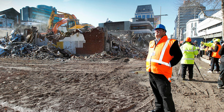 Earthquake Recovery Minister Gerry Brownlee watches demolition work on earthquake damaged buildings in Cashel Mall in Christchurch. Photo / Martin Hunter