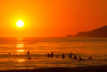 Surfers line up at sunset hoping to catch one last wave for the day. Photo / Thinkstock