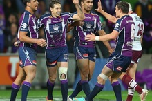 Billy Slater of the Storm is congratulated by team-mates after scoring a try. Photo / Getty Images