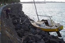 Paddy Evans looks over his stranded yacht at Tamaki Drive after its moorings broke in heavy seas on Saturday night.  Photo / Greg Bowker