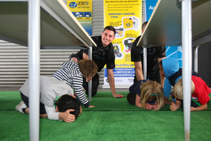 Breakers player Josh Bloxham helps Richard Road School pupils during an earthquake drill. Photo / Chris Gorman