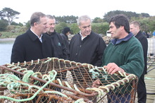 Prime Minister John Key, Chatham Islands general manager Owen Pickles, and Primary Industries Minister David Carter speak to local crayfish fisherman Noel Donaldson. Photo / Supplied
