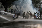 Pakistani police use water cannon to disperse protesters near the US Embassy in Karachi. Picture / AP