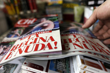 A newstands owner adjusts copies of the Italian magazine Chi reading in Italian 'The queen is naked'. Photo / AP