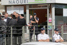 Members of the Jewish community talk in front of the kosher grocery store after the attack. Photo / AP