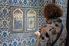 A member of the media examines a ceramic tile wall displayed in the new Islamic art section of the Louvre museum in Paris. Photo / AP