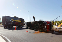 An injured driver had to be cut free after his truck and trailer overturned in Taupiri at a roundabout designed to improve safety. Photo / Christine Cornege