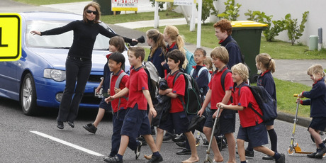 Children from the Bucklands Beach Primary School cross the road under the close guidance of a teacher. Photo / APN
