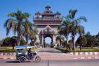 A tuk-tuk passes the Patuxai monument in Vientiane, Laos. Photo / Damian Christie