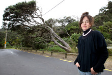 Megan Vertelle in front of the limb of the Piha pohutukawa tree she wants to save. Photo / Steven McNicholl